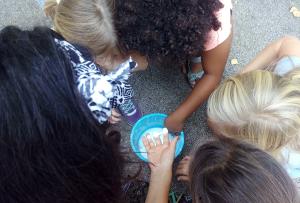 nens i nenes del casal experimentant amb aigua i Maizena